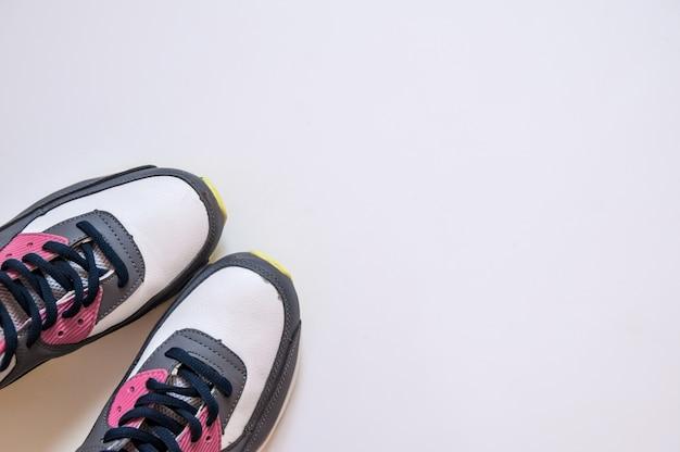Vista superiore delle scarpe da ginnastica su priorità bassa bianca. indumenti e attrezzature per il fitness. moda sportiva, accessori sportivi, attrezzatura sportiva. concetto sano stile di vita, sport e dieta. equipaggiamento sportivo.