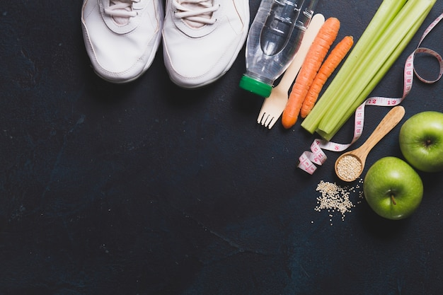 Top view of sneakers with vegetables and apples