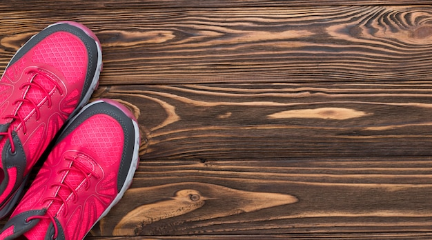 Top view of sneakers on wooden background with copy space