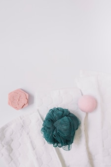 Top view of soap; bath bomb; loofah and napkin on white surface