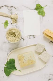 Top view of soap; salt; pumice stone; brush; ginkgo leaf and blank card on marble backdrop