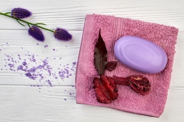 Мыло с полотенцем и цветами на белом столе, вид сверху