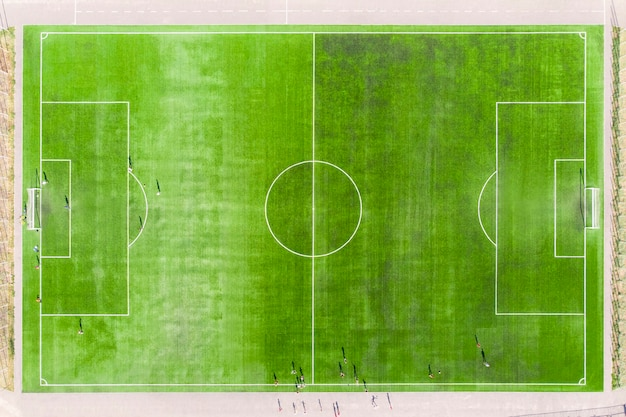 Top view of soccer field, football field. real football field aerial view. football players play on the mowed lawn at the stadium.