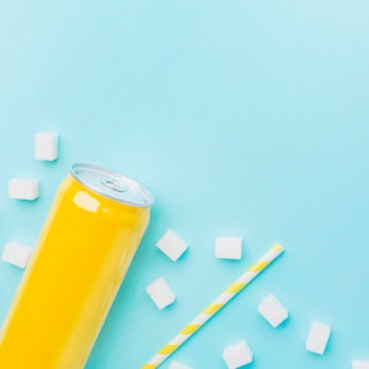 Top view of soft drink can with sugar cubes and straw