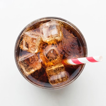Top view of soft drink in glass with ice cubes and straw