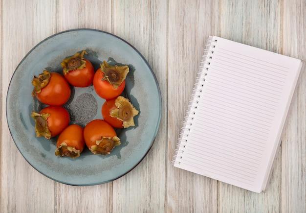 Vista dall'alto di cachi freschi morbidi su un piatto su un fondo di legno grigio con spazio di copia