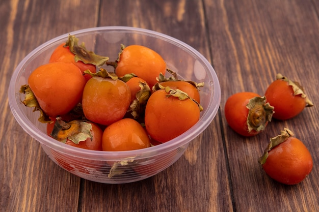 Top view of soft and juicy persimmons on a clear plastic bowl on a wooden surface