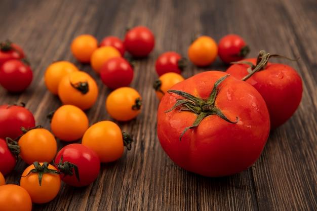 Vista dall'alto di morbidi pomodori rossi arrotondati con pomodorini arancioni e rossi isolati su una superficie di legno
