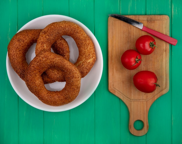 Top view of soft and sesame bagels on a plate with fresh tomatoes on a wooden kitchen board with knife on a green wooden background