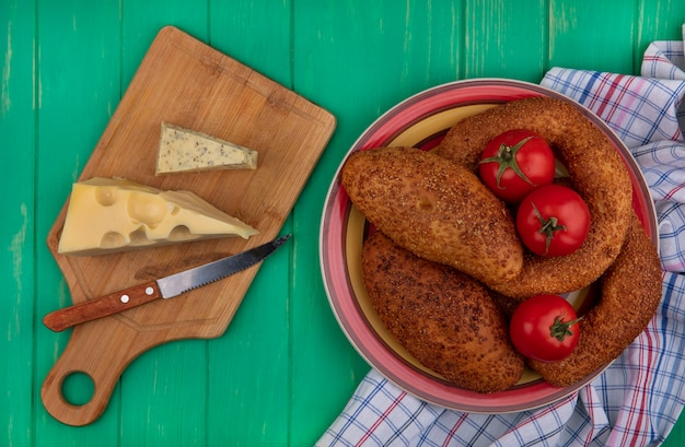 Vista dall'alto di polpette morbide e sesamo su una ciotola con pomodori freschi su un panno con formaggio su una tavola da cucina in legno con coltello su uno sfondo di legno verde