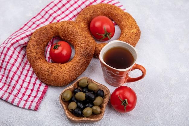 Vista dall'alto di morbidi bagel turchi con pomodori freschi e olive su una ciotola di legno su un panno rosso controllato su sfondo bianco