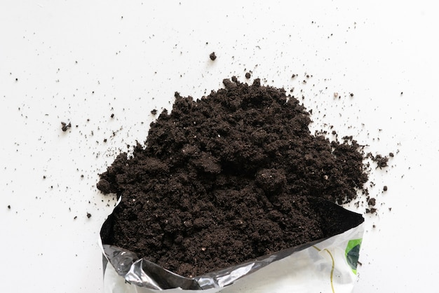 A top view of the soil dirt package to plante home flowers on the table