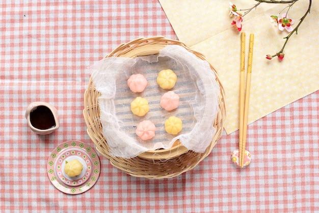 대나무 찜통과 나무 접시에 담긴 송편 떡(꿀을 채운 떡) 탑 뷰. 송편은 설날이나 한국의 감사절에 먹는 한국 전통 음식입니다.
