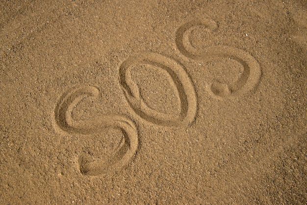 Top view of sos warning made on the brown sand