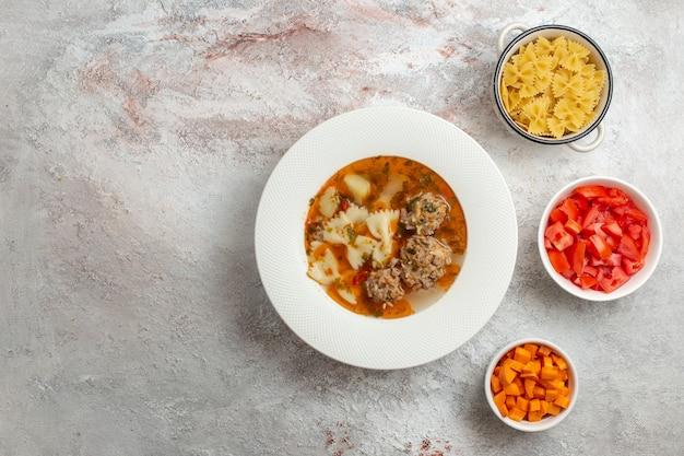 白い背景にスライスしたピーマンと肉のおいしいスープの上面図スープ