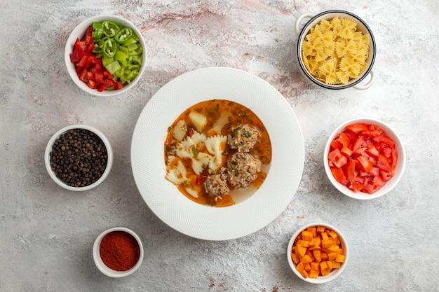 Вид сверху суп с мясом, вкусный суп с нарезанными овощами и приправами на белом фоне