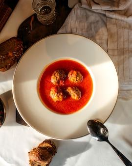 Вид сверху суп с мясом помидор вместе с ломтиками хлеба на белом полу