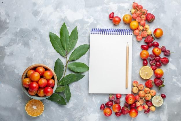 Vista dall'alto di amarene prugne con limone e altri frutti blocco note sulla scrivania leggera