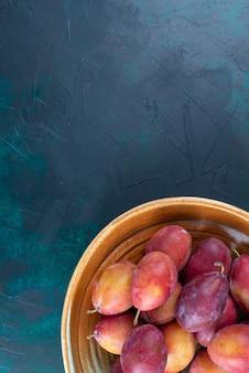 紺色の机の上の鍋の中の酸っぱい新鮮なプラムの上面図