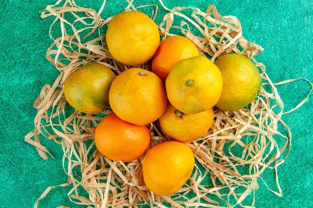 Вид сверху кислые свежие мандарины на зеленом фоне