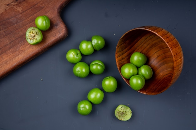 Top view of sour green plums scattered from a wooden bowl and wooden cutting board with sliced plums on black table