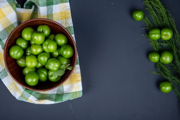 Top view of sour green plums in a wooden bowl on plaid napkin and scattered green plums with fennel on black table with copy space