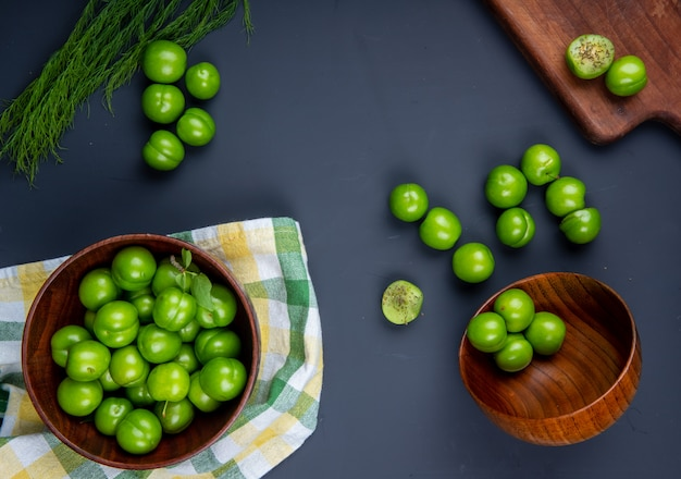 Top view of sour green plums in wooden bowls and wooden cutting board with sliced plums on black table