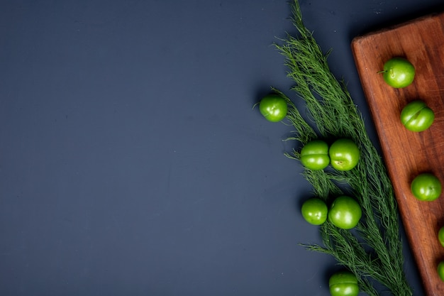 Top view of sour green plums on a wooden cutting board and fennel on black table with copy space