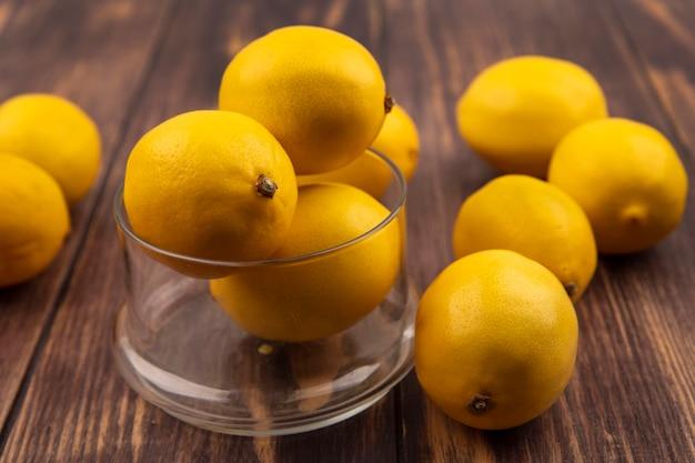 Vista dall'alto di limoni al gusto acido su una ciotola di vetro con limoni isolati su una superficie di legno