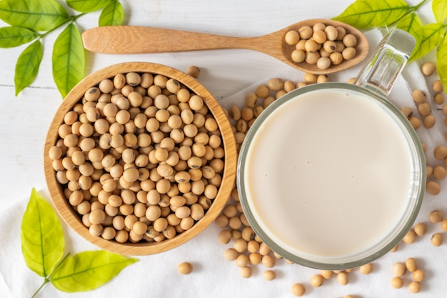 Top view of soya milk in a glass with soybeans in a wooden bowl