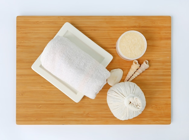 Top view spa herbal compressing ball with towels and salt scrub on wood board
