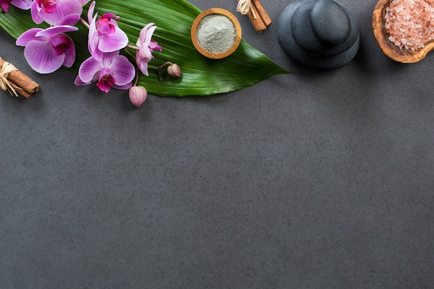Top view of spa setting with hot stones and orchids.