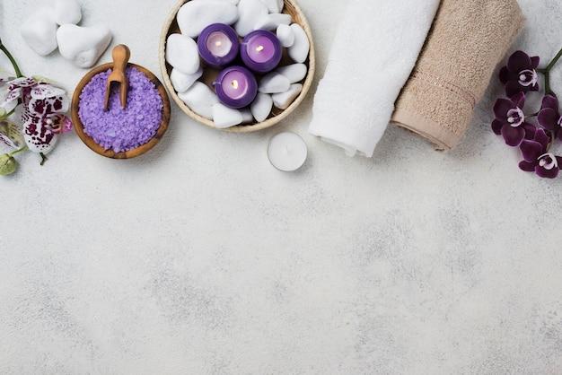Asciugamani e candele della stazione termale di vista superiore con lo spazio della copia