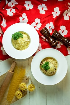 Top view of spaghetti bolognese with parmesan in a white bowl on colorful