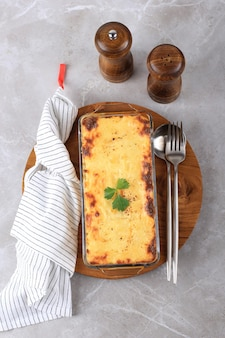 Top view spaghetti brulle on clear baking dish l with staiinless spoon and fork. spaghetti brulee is baked spaghetti with bechamel and bolognese sauce