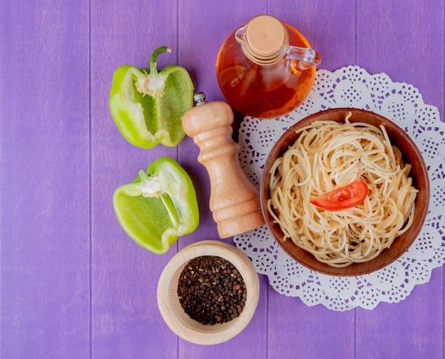 Vista superiore della pasta degli spaghetti in ciotola sul centrino di carta con mezzo sale pepe burro nero e pepe nero sul tavolo viola