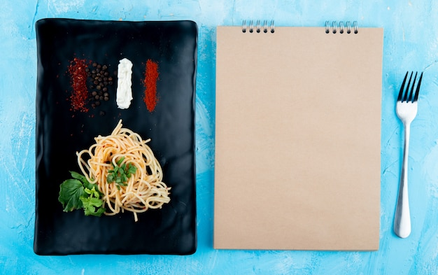 Top view of spaghetti pasta with basil and spices on a black platter and sketchbook on blue background