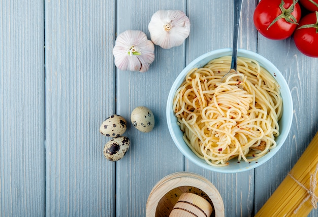 Top view of spaghetti pasta with chili flakes in a white bowl with fork fresh tomatoes garlic and quail eggs on wooden rustic background
