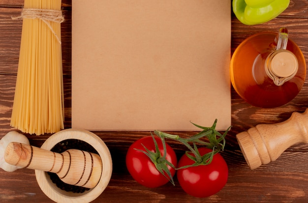 Top view of spaghetti pasta with ingredients around note pad on wooden surface with copy space