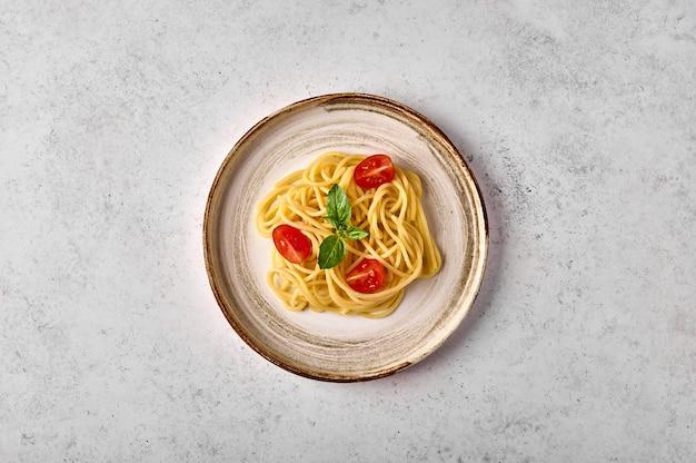Вид сверху спагетти паста с томатным черри, пармезаном и базиликом на керамической тарелке на свете