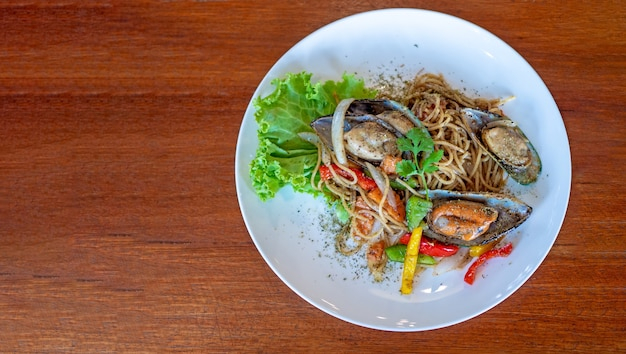 Top view of spaghetti with spicy mix seafood in white plate on the wooden background with copy space.