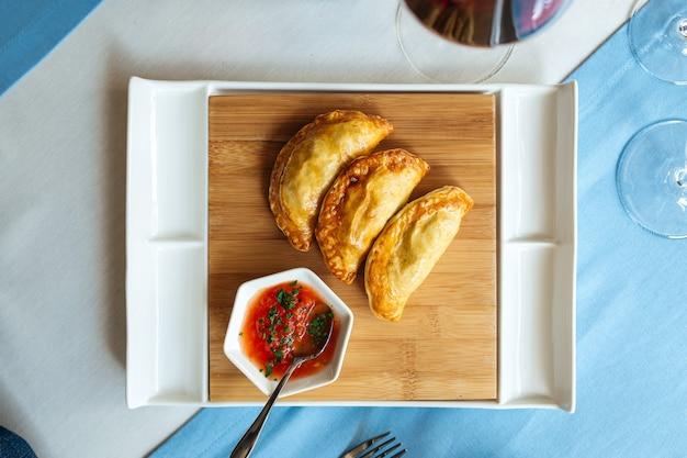 トップビューレストランのテーブルにソースとスペインのパイエンパナーダ