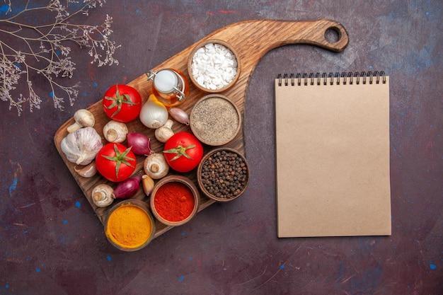 Vista dall'alto spezie sul tagliere spezie pomodori cipolle funghi e una bottiglia di olio sul tagliere e un quaderno