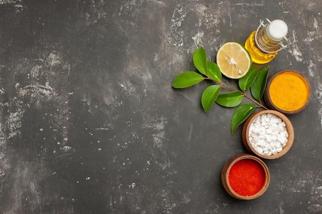Vista dall'alto ciotole di spezie colorate limone con foglie accanto alla bottiglia di olio sul lato destro del tavolo scuro
