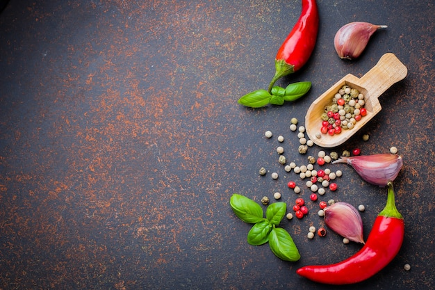 Top view of spices herbs. red pepper, garlic, basil leaves, pepper corns on dark concrete background