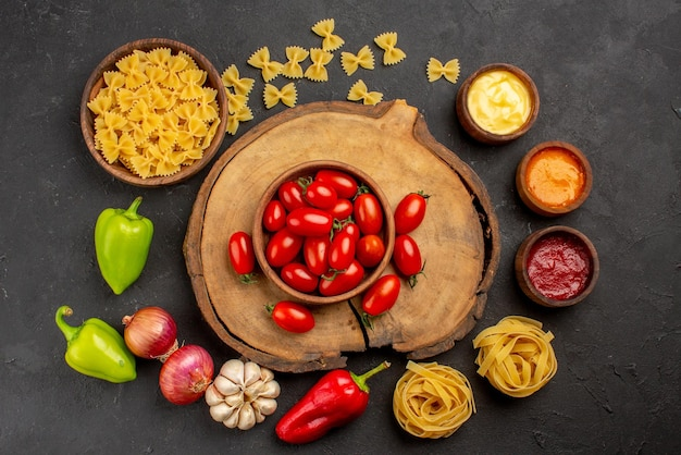 Top view spices pasta in bowl three kinds of sauce garlic onion red and green bell pepper next to the tomatoes on the wooden cutting board