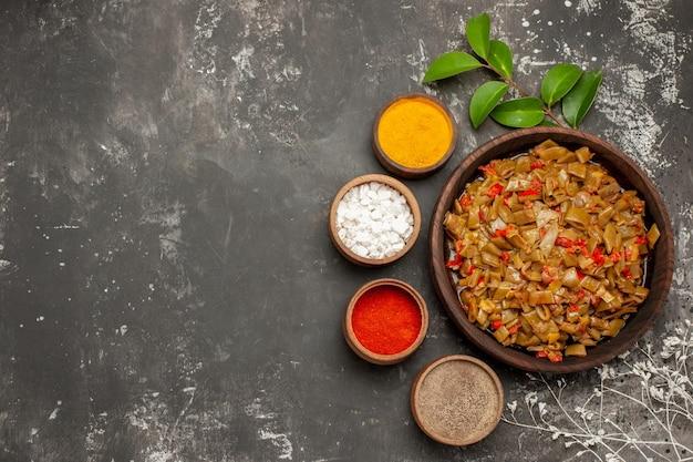 어두운 탁자에 있는 나뭇가지 옆에 다채로운 향신료 잎이 있는 그릇 옆에 있는 녹색 콩의 상위 뷰 향신료 접시