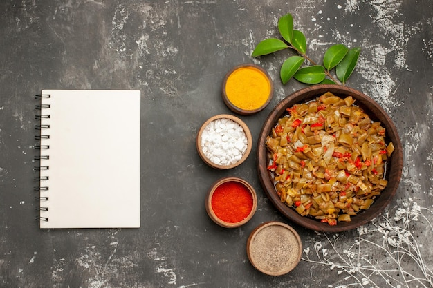 화려한 향신료 그릇 옆에 있는 녹색 콩의 상위 뷰 향신료 접시는 어두운 탁자에 있는 흰색 공책과 나뭇가지 옆에 있습니다.