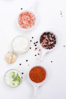 Вид сверху специи соль перец с чесноком и белым йогуртом на белой вертикали