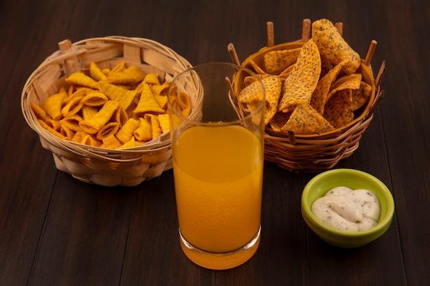 Vista dall'alto di patatine piccanti su un secchio con snack di mais su un secchio con un bicchiere di succo d'arancia con salsa su una ciotola verde su un tavolo di legno